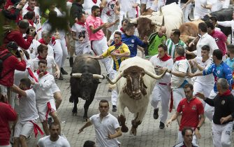 Participants run next to Puerto de San Lorenzo fighting bulls during the first bullrun of the San Fermin festival in Pamplona, northern Spain on July 7, 2019. - On each day of the festival six bulls are released at 8:00 a.m. (0600 GMT) to run from their corral through the narrow, cobbled streets of the old town over an 850-meter (yard) course. Ahead of them are the runners, who try to stay close to the bulls without falling over or being gored. (Photo by JAIME REINA / AFP) (Photo by JAIME REINA/AFP via Getty Images)