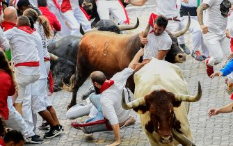 Participants fall next to Miura fighting bulls on the last bullrun of the San Fermin festival in Pamplona, northern Spain on July 14, 2018. - Each day at 8am hundreds of people race with six bulls, charging along a winding, 848.6-metre (more than half a mile) course through narrow streets to the city's bullring, where the animals are killed in a bullfight or corrida, during this festival dating back to medieval times and also featuring religious processions, folk dancing, concerts and round-the-clock drinking. (Photo by JOSE JORDAN / AFP)        (Photo credit should read JOSE JORDAN/AFP via Getty Images)