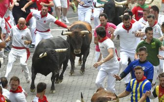 Participants run next to a Cebada Gago fighting bulls on the second bullrun of the San Fermin festival in Pamplona, northern Spain on July 8, 2019. - On each day of the festival six bulls are released at 8:00 a.m. (0600 GMT) to run from their corral through the narrow, cobbled streets of the old town over an 850-meter (yard) course. Ahead of them are the runners, who try to stay close to the bulls without falling over or being gored. (Photo by ANDER GILLENEA / AFP)        (Photo credit should read ANDER GILLENEA/AFP via Getty Images)