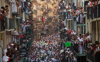 PAMPLONA, SPAIN - JULY 07:  Revellers run with Jandilla's fighting bulls along the Calle Estafeta during the second day of the San Fermin Running Of The Bulls festival on July 7, 2015 in Pamplona, Spain. The annual Fiesta de San Fermin, made famous by the 1926 novel of US writer Ernest Hemmingway entitled 'The Sun Also Rises', involves the daily running of the bulls through the historic heart of Pamplona to the bull ring.  (Photo by Pablo Blazquez Dominguez/Getty Images)