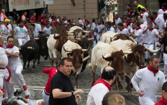 Participants run next to Cebada Gago fighting bulls on the second bullrun of the San Fermin festival in Pamplona, northern Spain on July 8, 2019. - On each day of the festival six bulls are released at 8:00 a.m. (0600 GMT) to run from their corral through the narrow, cobbled streets of the old town over an 850-meter (yard) course. Ahead of them are the runners, who try to stay close to the bulls without falling over or being gored. (Photo by JAIME REINA / AFP) (Photo by JAIME REINA/AFP via Getty Images)