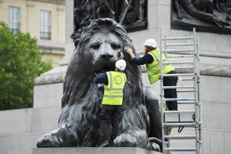 epa08530552 Workers clean lion sculptures at the base of Nelson's Column on Trafalgar Square in London, Britain, 06 July 2020. Pubs, restaurants, places of worship and other businesses reopened their doors across the UK on 04 July, after more than three months of lockdown due to coronavirus pandemic.  EPA/NEIL HALL