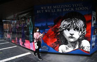 epa08530557 A masked woman passes a painting depicting the long running musical 'Les Miserables' in the West End of London, Britain, 06 July 2020. Britain's government has announced a 1.57bn pounds emergency support package to help protect the futures of theatres, galleries and museum across the country. Many arts institutions are facing financial difficulty due to the ongoing coronavirus pandemic.  EPA/NEIL HALL