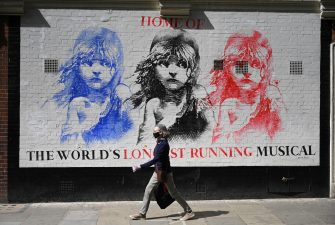 epa08530559 A masked woman passes a painting depicting the long running musical 'Les Miserables' in the West End of London, Britain, 06 July 2020. Britain's government has announced a 1.57bn pounds emergency support package to help protect the futures of theatres, galleries and museum across the country. Many arts institutions are facing financial difficulty due to the ongoing coronavirus pandemic.  EPA/NEIL HALL
