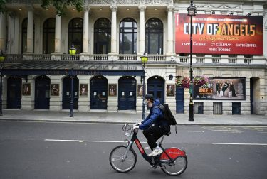 epa08530565 A masked cyclist passes the Garrick theatre in the West End of London, Britain, 06 July 2020. Britain's government has announced a 1.57bn pounds emergency support package to help protect the futures of theatres, galleries and museum across the country. Many arts institutions are facing financial difficulty due to the ongoing coronavirus pandemic.  EPA/NEIL HALL