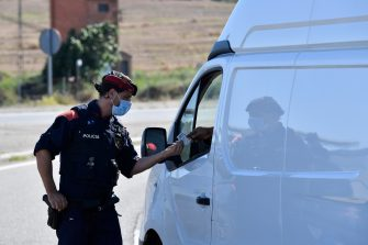 A member of the Catalan regional police force Mossos d'Esquadra controls a checkpoint on the road leading to Lleida on July 4, 2020. - Spain's northeastern Catalonia region locked down an area with around 200,000 residents around the town of Lerida following a surge in cases of the new coronavirus. (Photo by Pau BARRENA / AFP) (Photo by PAU BARRENA/AFP via Getty Images)