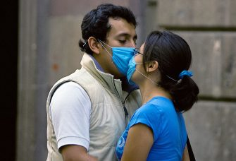 "A couple kisses at the Historic Center, in Mexico City, on April 25, 2009. An outbreak of deadly swine flu in Mexico and the United States has raised the specter of a new virus against which much of humanity would have little or no immunity. The outbreak of the new multi-strain swine flu virus transmitted from human to human that has killed up to 60 people in Mexico is a ""serious situation"" with a ""pandemic potential"", the head of the World Health Organization stated. AFP PHOTO/Alfredo Estrella (Photo credit should read ALFREDO ESTRELLA/AFP via Getty Images)"