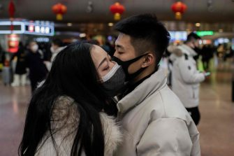 TOPSHOT - A couple, wearing protective masks, kisses goodbye as they travel for the Lunar New Year holidays, at Beijing West Railway Station in Beijing on January 24, 2020. - Chinese authorities rapidly expanded a mammoth quarantine effort aimed at containing a deadly contagion on January 24 to 13 cities and a staggering 41 million people, as nervous residents were checked for fevers and the death toll climbed to 26. (Photo by NICOLAS ASFOURI / AFP) (Photo by NICOLAS ASFOURI/AFP via Getty Images)