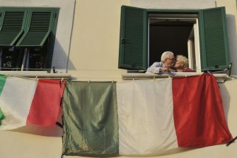 LIVORNO, ITALY - MARCH 30:  A couple kiss at the window of their home from which the flags of Italy are displayed during the quarantine on March 30, 2020 in Livorno, Italy.The Italian government continues to enforce the nationwide lockdown measures to control the spread of COVID-19. The number of confirmed Covid-19 cases in Italy has passed one hundred thousand today, (precisely 101,739) with the death toll rising to over 11,591.  (Photo by Laura Lezza/Getty Images)