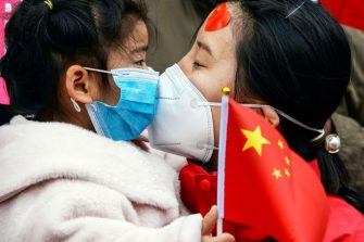 TOPSHOT - A medical staff member kisses her daughter after returning home from Wuhan helping with the COVID-19 coronavirus recovery effort, in Bozhou, in China's eastern Anhui province on April 10, 2020. (Photo by STR / AFP) / China OUT (Photo by STR/AFP via Getty Images)