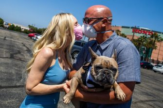 Chad Robbins and Tracey Robbins (R) kiss wearing face masks and holding their dog Huggy after their wedding ceremony officiated by a clerk recorder at the Honda Center parking lot on April 21, 2020 in Anaheim, California. - The County of Orange Clerk Recorder employees implemented a variety of social distancing techniques to safely issue licenses and marry couples during the novel coronavirus pandemic. (Photo by Apu GOMES / AFP) (Photo by APU GOMES/AFP via Getty Images)