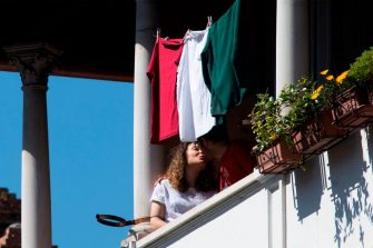 Residents in the Garbatella district of Rome kiss as they take part on April 25, 2020 in a 'Liberation Day' flashmob with people singing Italian partizan song 'Bella Ciao' from their window or balcony, during the country's lockdown aimed at curbing the spread of the COVID-19 infection, caused by the novel coronavirus. (Photo by Tiziana FABI / AFP) (Photo by TIZIANA FABI/AFP via Getty Images)