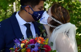 Newlyweds Rachel and Sebastian Vasquez share a kiss through their masks, following their wedding on May 9, 2020, at the Glencliff Manor in Rustburg, Virginia. - The Glencliff Manor officiates free, socially distanced ceremonies for couples left with no wedding plans during the coronavirus pandemic. Only ten people are allowed at each hour-long ceremony. (Photo by Olivier DOULIERY / AFP) (Photo by OLIVIER DOULIERY/AFP via Getty Images)