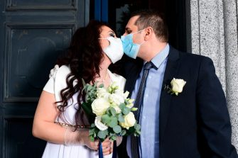 TOPSHOT - Newly-wed Italians Ester Concilio (L) and Rafaele Carbonelli kiss while wearing face masks following their wedding ceremony at the Briosco's town hall, about 45 km ( 28 miles) north of Milan, on May 11, 2020 during the country's lockdown aimed at curbing the spread of the COVID-19 infection, caused by the novel coronavirus. (Photo by Miguel MEDINA / AFP) (Photo by MIGUEL MEDINA/AFP via Getty Images)