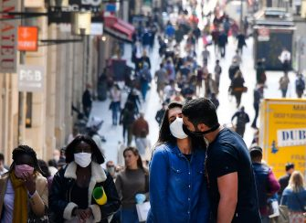 TOPSHOT - A couple wearingface mask walk kisses along the Sainte Catherine street, on May 15, 2020 in Bordeaux, as the lockdown introduced two months ago to fight the spread of the Covid-19 disease caused by the novel coronavirus is progressively easing. (Photo by GEORGES GOBET / AFP) (Photo by GEORGES GOBET/AFP via Getty Images)