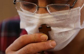 A Christian worshipper, wearing a protective mask due to the COVID-19 pandemic, kisses a cross as he prays at the Mart Shmoni church in Arbil, the capital of the autonomous Kurdish region of northern Iraq, on May 17, 2020. (Photo by SAFIN HAMED / AFP) (Photo by SAFIN HAMED/AFP via Getty Images)