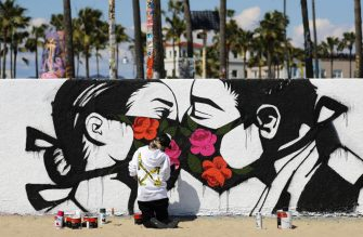 VENICE, CALIFORNIA - MARCH 21: Artist Pony Wave paints a scene depicting two people kissing while wearing face masks on Venice Beach on March 21, 2020 in Venice, California. California Governor Gavin Newsom issued a â  stay at homeâ   order for Californiaâ  s 40 million residents  in order to slow the spread of coronavirus (COVID-19). Californians may still go to the beach without violating Newsomâ  s order as long as they maintain social distancing and adhere to other public health measures related to the coronavirus. (Photo by Mario Tama/Getty Images)