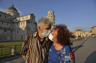 PISA, ITALY - MAY 30:  An eldery couple wearing face masks pose for a photograph while kissing near the tower of Pisa on May 30, 2020 in Pisa, Italy. The city of Pisa in Piazza dei Miracoli celebrated the reopening of the Tower of Pisa and of the city to the world with a Flash Mob after the long lockdown due to the Coronavirus. There have been over 232,000 reported COVID-19 cases in Italy and more than 33,000 deaths.  (Photo by Laura Lezza/Getty Images)