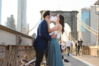 NEW YORK, NEW YORK - MAY 16: A couple kiss while wearing face masks on Brooklyn Bridge during the coronavirus pandemic on May 16, 2020 in New York City. COVID-19 has spread to most countries around the world, claiming over 313,000 lives with over 4.7 million infections reported. (Photo by Noam Galai/Getty Images)