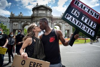 MADRID, SPAIN - JUNE 07: An interracial couple kiss in front of 'Puerta de Alcala' as they hold placards reading (L-R) 'you're either an anti-racist or a racist' and 'racism is the pandemic' during a Black Lives Matter protest that took place outside the Embassy of the United States in Madrid following the death of George Floyd on June 07, 2020 in Madrid, Spain. The death of an African-American man, George Floyd, while in the custody of Minneapolis police has sparked protests across the United States, as well as demonstrations of solidarity in many countries around the world. Spain has largely ended the lockdown it imposed to curb the spread of Covid-19, which caused the death of more than 27,000 people across the country. (Photo by Pablo Cuadra/Getty Images)