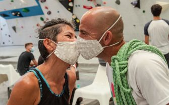 "SEVILLE, SPAIN - JUNE 22: Couple of climber Encarnación and Juan poses for a kiss with protective masks after a training session at Rock&wall Climbing Gym on the day of reopening after the lockdown on June 22, 2020 in Seville, Spain. The reopening measures include obligatory use of liquid chalk for every climber, 1,5 meters of security distance, no presence on the mats for other climbers and the use of protective masks to avoid the spread of Covid-19. Capacity is now at 65%, according to the last disposition of the Government of Andalucia, and is now fixed at 135 people. Seven out of ten workers are back from the temporary labor force adjustment (""Erte"" in Spanish). The remaining three workers are expected to return in September, when the gym will reactivate courses and other group activities. According to the business the coronavirus crisis has interrupted 13 weeks of activities, from March 13th until today. The pandemic  hit at the beginning of the spring, which has been historically the best season for this climbing gym business. (Photo by Niccolo Guasti/Getty Images)"