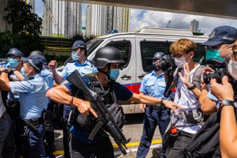 HONG KONG, CHINA - JULY 06: Police stand guard as defendant Tong Ying-kit, 23, arrives the court - Tong accused of deliberately driving his motorcycle into a group of police officers, is the first person charged for incitement to secession and terrorist activities under the national security law, on July 6, 2020 in Hong Kong, China. (Photo by Billy H.C. Kwok/Getty Images)