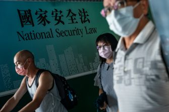 HONG KONG, CHINA - JUNE 30: Pedestrians walk past a government-sponsored advertisement promoting a new national security law on June 30, 2020 in Hong Kong, China. Beijing has passed the controversial national security law which will threaten the city's autonomy and political freedoms.  (Photo by Anthony Kwan/Getty Images)