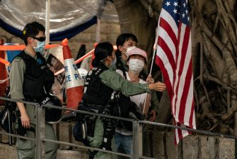HONG KONG, CHINA - JULY 04: Riot police deter a woman as she display a US flag to celebrate the declaration of Independence of the United States outside the US Consulate General on July 4, 2020 in Hong Kong, China. Hong Kong marked the 23rd anniversary of the handover of the former British colony to China on July 1 hours after Beijing imposed the new national security law.  (Photo by Anthony Kwan/Getty Images)