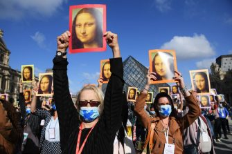 PARIS, FRANCE - JULY 06: Visitors hold reproductions of the Mona Lisa outside the Louvre museum as it reopens its doors following its 16 week closure due to lockdown measures caused by the COVID-19 coronavirus pandemic, at the Louvre on July 6, 2020 in Paris, France. (Photo by Pascal Le Segretain/Getty Images)