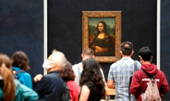 """Visitors wearing face masks take pictures in front of Leonardo da Vinci's masterpiece  """" Mona Lisa """" also known as """" La Gioconda """"  held in the Salle des  Etats, at the Louvre Museum in Paris on July 6, 2020, on the museum' s reopening day. - The Louvre museum will reopen its doors on July 6, 2020, after months of closure due to lockdown measures linked to the COVID-19 pandemic, caused by the novel coronavirus. The coronavirus crisis has already caused """"more than 40 million euros in losses"""" at the Louvre, announced its president and director Jean-Luc Martinez, who advocates a revival through """"cultural democratization"""" and is preparing a """"transformation plan"""" for the upcoming Olympic Games in 2024. (Photo by FRANCOIS GUILLOT / AFP) (Photo by FRANCOIS GUILLOT/AFP via Getty Images)"""