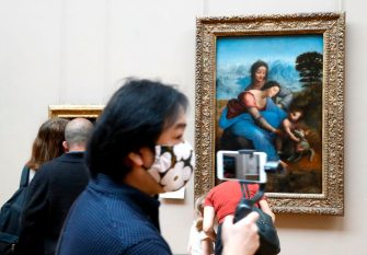 """A visitor wearing face mask walks past  """" The Virgin and Child with Saint Anne """" oil painting by Leonardo da Vinci, at the Louvre Museum in Paris on July 6, 2020, on the museum' s reopening day. - The Louvre museum will reopen its doors on July 6, 2020, after months of closure due to lockdown measures linked to the COVID-19 pandemic, caused by the novel coronavirus. The coronavirus crisis has already caused """"more than 40 million euros in losses"""" at the Louvre, announced its president and director Jean-Luc Martinez, who advocates a revival through """"cultural democratization"""" and is preparing a """"transformation plan"""" for the upcoming Olympic Games in 2024. (Photo by FRANCOIS GUILLOT / AFP) (Photo by FRANCOIS GUILLOT/AFP via Getty Images)"""