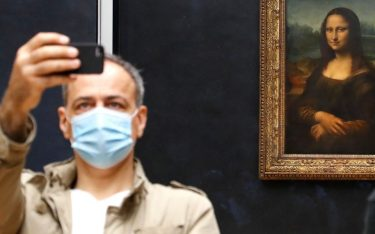 """A visitor wearing face mask take a pictures in front of Leonardo da Vinci's masterpiece  """" Mona Lisa """" also known as """" La Gioconda """"  held in the Salle des  Etats, at the Louvre Museum in Paris on July 6, 2020, on the museum' s reopening day. - The Louvre museum will reopen its doors on July 6, 2020, after months of closure due to lockdown measures linked to the COVID-19 pandemic, caused by the novel coronavirus. The coronavirus crisis has already caused """"more than 40 million euros in losses"""" at the Louvre, announced its president and director Jean-Luc Martinez, who advocates a revival through """"cultural democratization"""" and is preparing a """"transformation plan"""" for the upcoming Olympic Games in 2024. (Photo by FRANCOIS GUILLOT / AFP) (Photo by FRANCOIS GUILLOT/AFP via Getty Images)"""