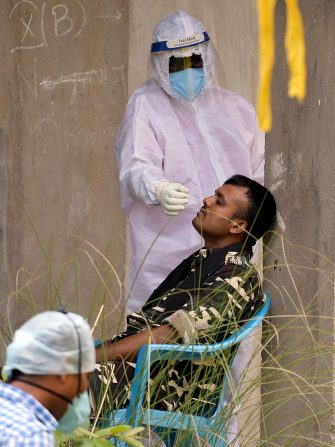 epa08530658 An Indian paramilitary personnel gets his swab test done at a Covid-19 screening during the total lockdown in Guwahati, India, 06 July 2020. Guwahati is the worst coronavirus-affected city in Assam and began a strict, two-week lockdown from the evening of 28 June 2020.  EPA/STR