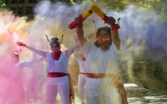 Pro-animal rights activists spread powder to celebrate the cancellation of the San Fermin Festival's bullfights and bull-running during a demonstration called by the People for the Ethical Treatment of Animals (PETA) and Anima Naturalis pro-animal groups in Pamplona, on July 7, 2020. - The 2020 edition of the San Fermin Festival has been cancelled as part of preventive measures to fight the spread of the novel coronavirus. (Photo by ANDER GILLENEA / AFP) (Photo by ANDER GILLENEA/AFP via Getty Images)