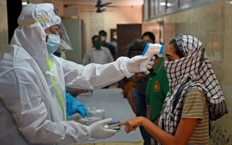 A medical volunteer wearing Personal Protective Equipment (PPE) gear takes temperature reading of a woman during a medical screening for the COVID-19 coronavirus, at a residential society in Mumbai on July 10, 2020. - Hospitals in densely populated cities such as Mumbai and Delhi are struggling to cope with the epidemic, and the country now has around 720,000 infections -- the world's third-highest. (Photo by Punit PARANJPE / AFP) (Photo by PUNIT PARANJPE/AFP via Getty Images)