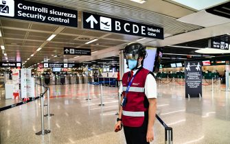 "A Fiumicino airport employee wearing a ""Smart-Helmet"" portable thermoscanner to screen passengers and staff for COVID-19, stands prepared at boarding gates on May 5, 2020 at Rome's Fiumicino airport during the country's lockdown aimed at curbing the spread of the COVID-19 infection, caused by the novel coronavirus. (Photo by ANDREAS SOLARO / AFP) (Photo by ANDREAS SOLARO/AFP via Getty Images)"