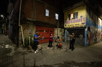 SAO PAULO, BRAZIL - JULY 08: String quartet formed by students from the Baccarelli Institute plays in the street in Heliopolis amidst the coronavirus (COVID-19) pandemic on July 8, 2020 in Sao Paulo, Brazil. Instituto Baccarelli is a non-profit organization that teaches music to more than 1200 underprivileged and socially vulnerable children and young people in Heliopolis, one of the biggest favelas in Sao Paulo of over 200,000 inhabitants. The Institute is responsible for creating the first orchestra in the world that emerged in a favela, the Heliopolis Symphonic Orchestra. With the social and economic impact of the coronavirus (COVID-19) pandemic in these poor communities, Instituto Baccarelli decided to raise funds and the donations are used for food, cleaning and hygiene products. (Photo by Alexandre Schneider/Getty Images)