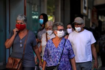 People wear face masks at the Tijuca neighborhood in Rio de Janeiro, Brazil on July 8, 2020, amid the new coronavirus pandemic. - Brazilian President Jair Bolsonaro has tested positive for the coronavirus after months of downplaying the dangers of the disease. (Photo by MAURO PIMENTEL / AFP) (Photo by MAURO PIMENTEL/AFP via Getty Images)