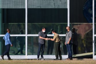 A guard gives a mobile phone to Brazilian President Jair Bolsonaro (2-L) outside Alvorada Palace in Brasilia on July 10, 2020. - Brazilian President Jair Bolsonaro tested positive for the coronavirus after months of downplaying the dangers of the disease. (Photo by EVARISTO SA / AFP) (Photo by EVARISTO SA/AFP via Getty Images)