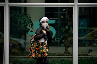 A woman wearing a face mask and shield speaks on her mobile phone as she walks at the Botafogo neighborhood in Rio de Janeiro, Brazil on July 10, 2020, amid the new coronavirus pandemic. (Photo by MAURO PIMENTEL / AFP) (Photo by MAURO PIMENTEL/AFP via Getty Images)