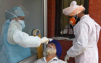 Health officials collect a nasal swab sample from a man to test for the COVID-19 coronavirus, at a civil hospital in Amritsar on July 10, 2020. - India on July 6 became the country with the third-highest coronavirus caseload in the world, as a group of scientists said there was now overwhelming evidence that the disease can be airborne -- and for far longer than originally thought. (Photo by NARINDER NANU / AFP) (Photo by NARINDER NANU/AFP via Getty Images)