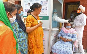 Health officials collect a nasal swab sample from a woman to test for the COVID-19 coronavirus, as people wait for their turn at a civil hospital in Amritsar on July 10, 2020. - India on July 6 became the country with the third-highest coronavirus caseload in the world, as a group of scientists said there was now overwhelming evidence that the disease can be airborne -- and for far longer than originally thought. (Photo by NARINDER NANU / AFP) (Photo by NARINDER NANU/AFP via Getty Images)