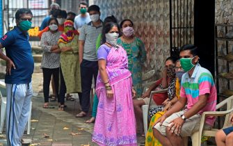 Residents wait for their turn to get screened during a medical screening for the COVID-19 coronavirus, at a residential society in Mumbai on July 10, 2020. - Hospitals in densely populated cities such as Mumbai and Delhi are struggling to cope with the epidemic, and the country now has around 720,000 infections -- the world's third-highest. (Photo by Punit PARANJPE / AFP) (Photo by PUNIT PARANJPE/AFP via Getty Images)