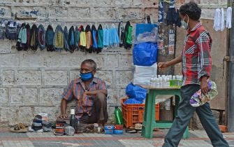 A pedestrian walks past a cobbler selling facemasks and sanitizers on the roadside after the authorities eased restrictions imposed as a preventive measure against the spread of the COVID-19 coronavirus, in Hyderabad on July 10, 2020. - Around the world, governments are struggling to balance the need to reopen economies wrecked by weeks of lockdown measures against the risk of new COVID-19 coronavirus infections as people return to normal life. (Photo by NOAH SEELAM / AFP) (Photo by NOAH SEELAM/AFP via Getty Images)