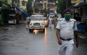 Police personnel patrol on a street shut after a recent lockdown was reimposed in nine wards under Siliguri Municipal area as a preventive measure against the COVID-19 coronavirus in Siliguri on July 10, 2020. (Photo by Diptendu DUTTA / AFP) (Photo by DIPTENDU DUTTA/AFP via Getty Images)