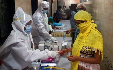 Medical volunteers wearing Personal Protective Equipment (PPE) gear distribute Vitamin tablets to the residents after their medical screening for the COVID-19 coronavirus, at a residential society in Mumbai on July 10, 2020. - Hospitals in densely populated cities such as Mumbai and Delhi are struggling to cope with the epidemic, and the country now has around 720,000 infections -- the world's third-highest. (Photo by Punit PARANJPE / AFP) (Photo by PUNIT PARANJPE/AFP via Getty Images)