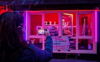 HAMBURG, GERMANY - JULY 11: A woman takes a photo as sex workers protest against lockdown measures that are preventing brothels from reopening in Hamburg's red light district during the coronavirus pandemic on July 11, 2020 in Hamburg, Germany. Sex workers across Germany are demanding an easing of ongoing lockdown measures that are preventing them from resuming their work. While authorities have lifted lockdown measures for most businesses in Germany, some, especially for those that involve close physical contact, remain in place. Legal sex workers say they are being treated unfairly, claiming they have developed adequate hygienic measures to prevent the spread of the virus and point out that other businesses that require similar physical proximity, such as hair salons and tattoo parlours, have been allowed to reopen. (Photo by Morris MacMatzen/Getty Images)