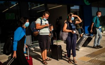 Passengers of a flight from Budapest wearing protective face masks arrive at the Corfu Airport Ioannis Kapodistrias on Corfu Island on July 1, 2020, on its reopening day following months of closure due to the sanitary measures taken to curb the spread of the Covid-19 disease caused by the novel coronavirus. - Greece on July 1, 2020 reopened flights to its flagship island destinations as it raced to salvage a portion of the annual tourism season that is vital to its economy. (Photo by ANGELOS TZORTZINIS / AFP) (Photo by ANGELOS TZORTZINIS/AFP via Getty Images)