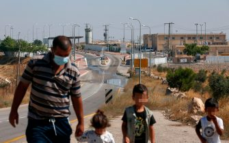 Palestinian Othman Abu Qbeita walks with his children towards their home in Al-Issifer Palestinian village, past the Israeli checkpoint entrance of Metzodot Yahoda near the settlement of Yattir overlooking his village, south of Yatta town, in the occupied West Bank, on July 12 ,2020. - Othman who lives with his family in Al-Issifer village, needs a special permit from the Israeli army to reach his home as he has to cross a checkpoint only used for Israelis to access settlements and other cities as well as Israel's south. (Photo by HAZEM BADER / AFP) (Photo by HAZEM BADER/AFP via Getty Images)