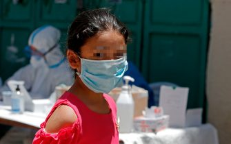 A Palestinian girl wears a face mask as medical workers affiliated with the Palestinian health ministry collect samples to test for the Covid-19 coronavirus in a mobile position in al-Azza Refugee Camp in the West Bank city of Bethlehem, on June 24, 2020. - Coronavirus cases in the West Bank have more than doubled in a week, the Palestinian Authority said after warning a second wave of infections could be worse than the first. (Photo by Musa Al SHAER / AFP) (Photo by MUSA AL SHAER/AFP via Getty Images)